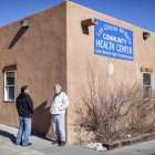 While waiting for Las Clinicas Del Norte in Abiquiú to open, Leonard Ferran, right, and Alanzo Gallegos talk. The community health center serves everyone, regardless of whether they are insured. The clinic would be available to people who receive insurance through the proposed health insurance exchange. (Craig Fritz/New Mexico In Depth)