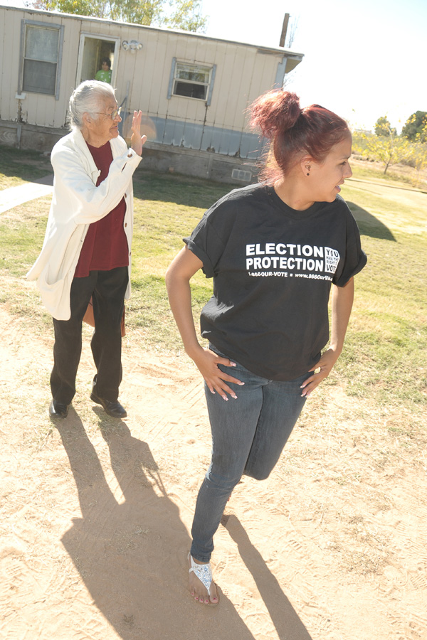 Alejandra Gomez, 21, walks with 86-year-old Maria Prieto from Prieto's home in Chaparral to a pickup truck parked out front. Gomez and another activist took Prieto and her husband to a nearby polling place on Election Day in November so they could vote. (Photo by Steve MacIntyre/New Mexico In Depth)