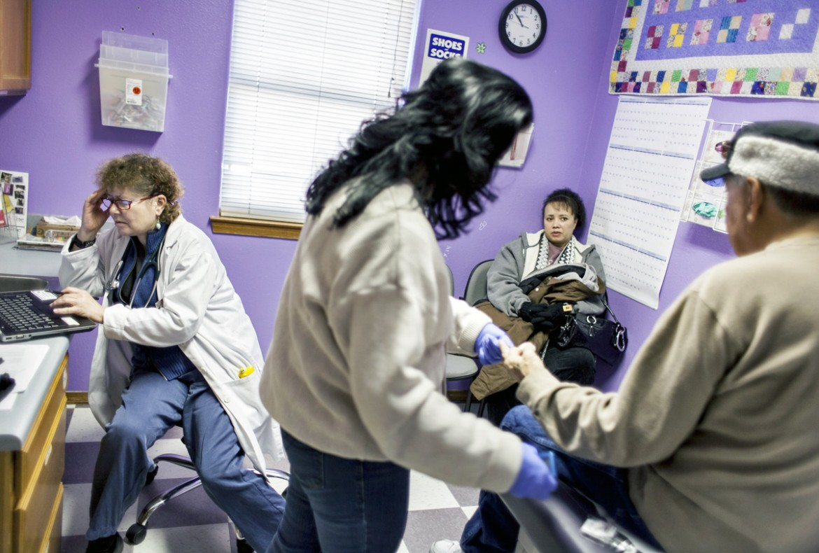 """Dr. Suzanne Norman, left, looks over medical records while Cindy Garcia watches Elaine Valdez draw blood from her husband, Leroy Garcia, at Las Clinicas Del Norte in Abiquiú. A decision by Gov. Susana Martinez to expand Medicaid could exacerbate an existing provider shortage in New Mexico. """"I can't imagine being busier,"""" Norman says. (Craig Fritz/New Mexico In Depth)"""