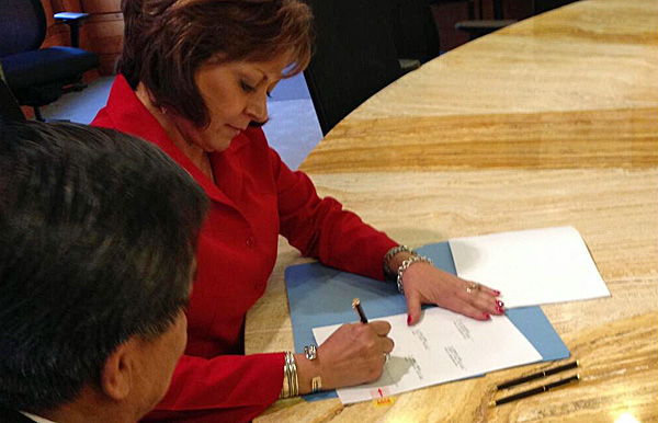 Gov. Susana Martinez signs Senate Bill 221, establishing the state health insurance exchange, into law earlier today. Sen. Benny Shendo, D-Jemez Pueblo and the bill's primary sponsor, is at left. (Photo courtesy of Matt Kennicott/N.M. Human Services Department)