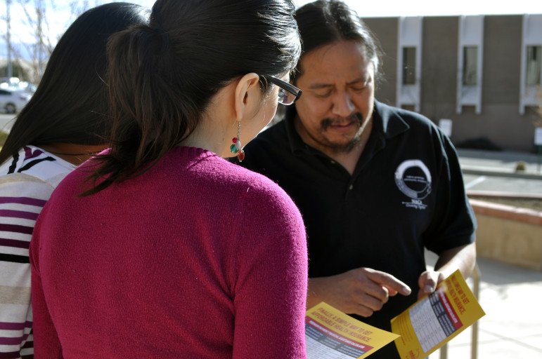 """Sonny Weahkee, a health guide working to sign Native Americans up for health insurance, demonstrates his outreach """"rap"""" with coworkers outside the nonprofit's headquarters in Albuquerque."""