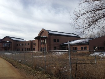 Mora County's new two-story courthouse sits unfinished behind a chainlink fence. It's often cited as an example of the flaws in the state's capital funding process. Sandra Fish/New Mexico In Depth