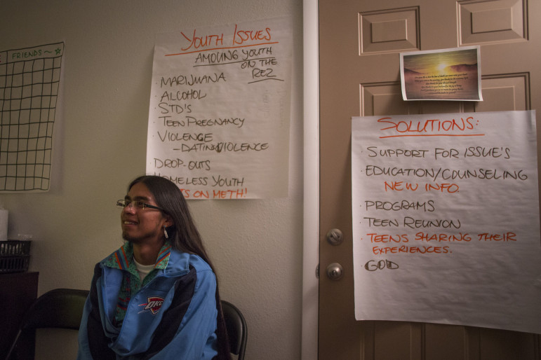 Coloradas Mangas talks with a coworker at the community health center office in Mescalero. Signs outlining youth issues and solutions adorn the walls.