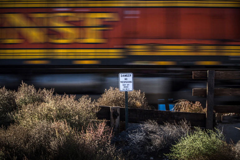 A sign warns people to stay away as a freight train passes through Grants in November 2014.