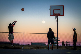 The moon rises over Thoreau as Hector Largo, left, takes a jump shot, while, Jacob James, center, and Damarco Pierce, right, await the rebound at the Thoreau Community Center basketball court in November 2014. The boys hung out at the center after school, working on homework and shooting hoops before a youth board meeting that evening.