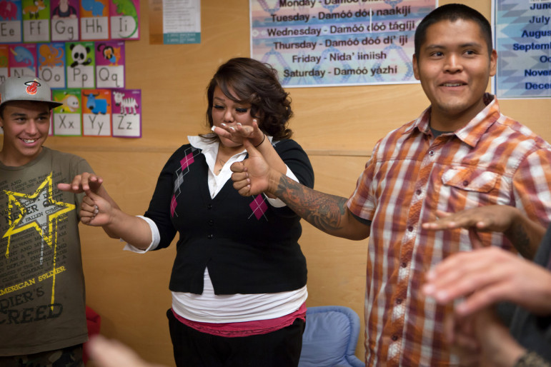 Alex Begay, right, with the National Indian Youth Leadership Project, leads a group ice-breaking activity at the beginning of a youth board meeting at the Thoreau Community Center on Nov. 5, 2014. To the left of Begay are Damarco Pierce, wearing a cap, and Raelynn Hill. Both are Youth Board members.
