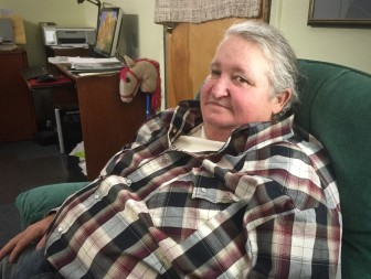 Sherrie Cline sits in the parish office at Holy Family Church, where she got help with title loan debt.