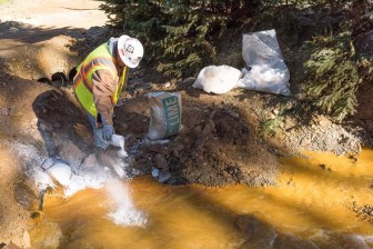 As water exits the mine, it flows into a system of four treatment ponds. The treatment ponds provide retention time to allow the pH to adjust. Here, lime is added to a settling pond to assist in the pH adjustment of the water prior to discharge to Cement Creek on Aug 14, 2015. (Credit: Eric Vance/EPA)