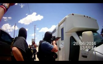Still frame made from an APD officer's body-worn camera when police stormed a mobile syringe exchange on June 28. The van is the exchange. The men in masks are officers. The woman with her hands up is a Health Care for the Homeless worker.