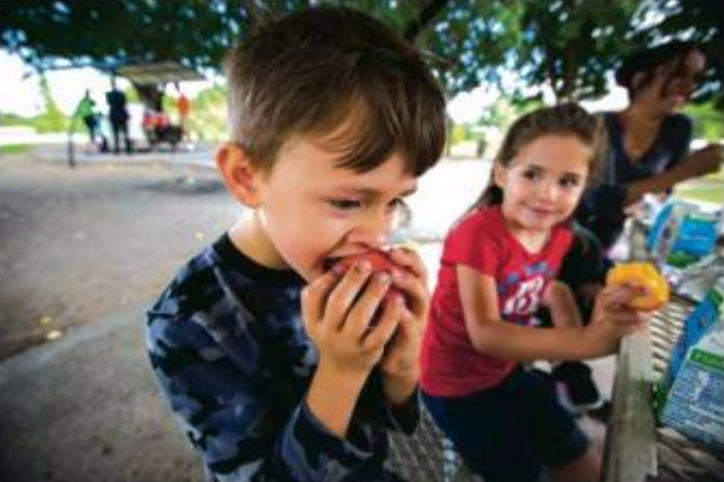 5-year old Seth Potts bites into a peach provided as part of a free lunch by Families and Youth, Inc. at Young Park in Las Cruces while 5-year old Vivian Trivizo looks on, June 1, 2016. The free lunch program is funded through the New Mexico Children, Youth and Families Department.